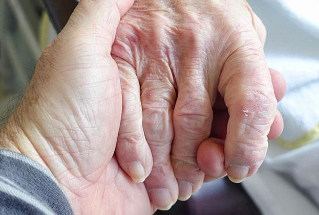 Eine jüngere Person hält die Hand einer älteren Person. Das gibt Senioren Kraft, wenn sie wissen, sie werden nicht alleine gelassen.